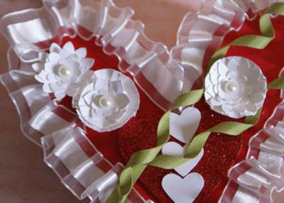 A closeup of the flowers, ribbon,  and stems on the heart shaped box...